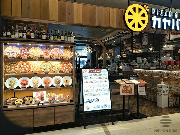Models of pizza and other dishes are put at an angle of 45-60 degrees in Italian restaurant display window. This way, customers can study the menu better.