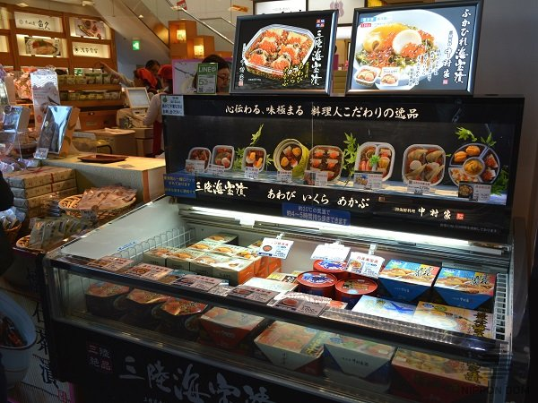 Replicas of fresh cooked food in a showcase with frozen foods attract customers' attention.