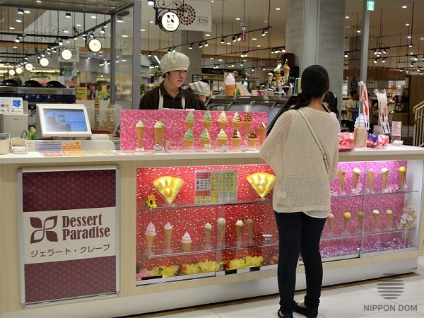 Pink display window with ice cream in a mall attracts attention of visitors with children.