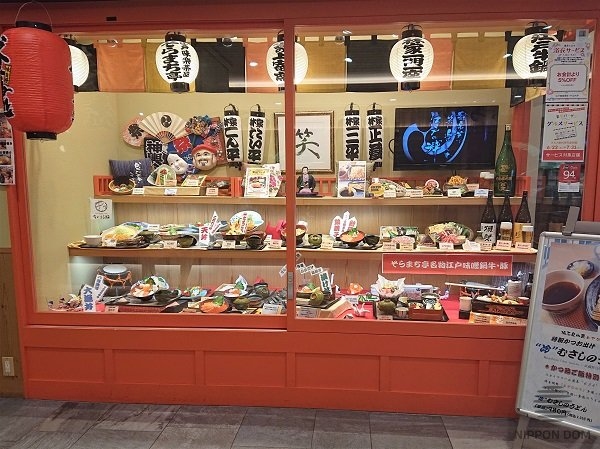 Japanese cultural items are located in sushi restaurant display window: masks, dolls, hand fans, lanterns, pictures.