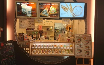 Food models in a display window decorate fast food restaurant facade and catch people's interest.