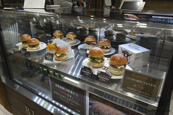 Рядом с муляжами бургеров выставлены образцы упаковки для покупки на вынос