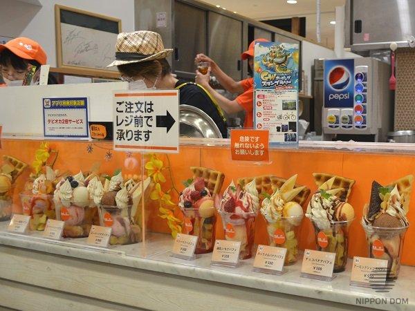 На витрине фастфуд представлены муляжи десертов в стаканчиках двух размеров