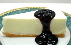 A replica of cheesecake with bilberry sauce