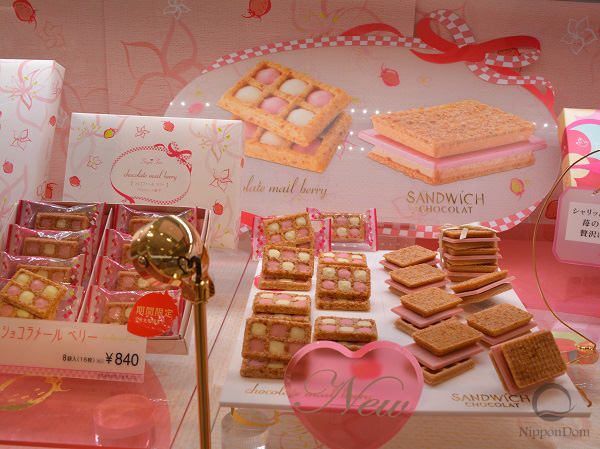 Big photos of strawberry cookies on the background decorate display window and capture attention of supermarket visitors.