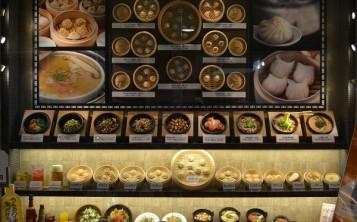 Яркие плакаты с увеличенными блюдами украшают витрину с муляжами