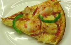 A slice of pizza with shrimp and green pepper